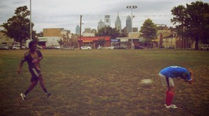 Philadelphia Union player Michael Lahoud kicks a soccer ball at the backside of STHM Professor Thilo Kunkel for the Kick Ebola in the Butt Challenge. (Courtesy Thilo Kunkel)