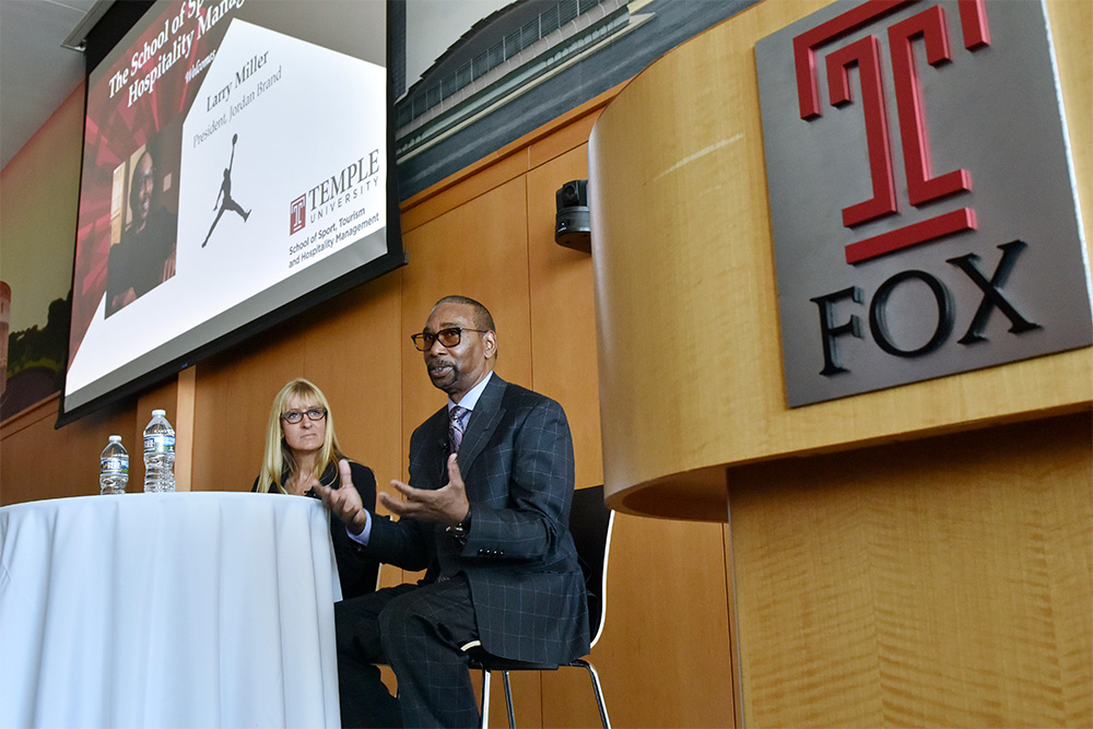 Larry Miller, President of Nike's Jordan Brand, answers a question from Lara Price, Senior Vice President of Business Operations with the Philadelphia 76ers, during the question-and-answer segment of Miller's visit as STHM Executive in Residence